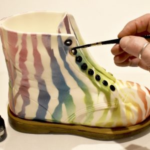 Paint each eyelet with black metallic food paint using a fine brush.