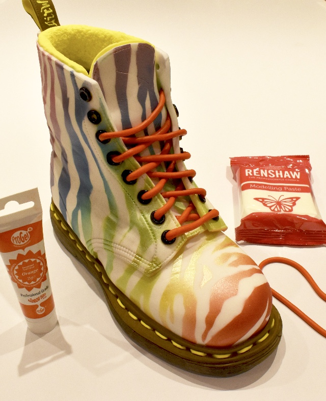 Mix orange Pro Gel colour into 40g of Renshaw modelling paste. Roll out two long sausage strips to make laces for the boot. Cut each section and glue in place starting from the bottom of the lace inserting into each eyelet.