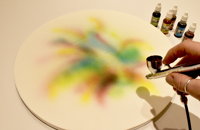 Roll out the remaining white Renshaw extra sugarpaste and cover a 16 inch round cake board. Spray on various rainbow colours with an airgun making an outward rainbow splash effect using Rainbowdust (colour Flo) airbrush colours. Leave board set and dry before attaching the boot.