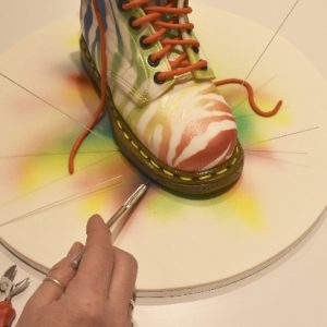 Attach the finished boot to the board with Royal icing to glue in place. Insert a scribe needle pushed in at an angle into the cake board to make a pilot hole for the wire support. Cut 22 gauge florist wire to various lengths for the colour splashes.