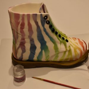 Attach the boot to the sole with edible glue. Roll out the remaining Khaki sugarpaste to 3mm thick and cut into 5mm wide strips and glue around the edge of the sole.